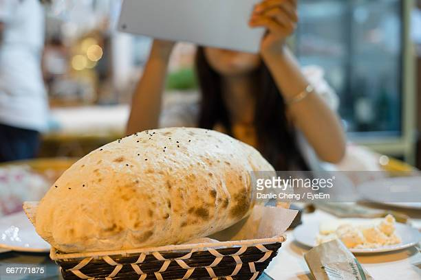 Close-Up Of Puffed Roti With Woman Using Technology In Background