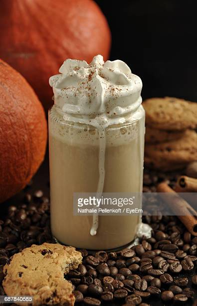 Close-Up Of Pumpkin Spice Latte And Roasted Coffee Beans