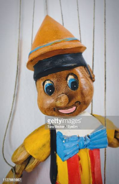 close-up of puppet against white wall - pinocchio stock pictures, royalty-free photos & images