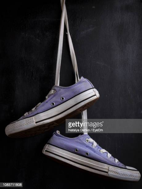 close-up of purple canvas shoes against black background - purple shoe stock pictures, royalty-free photos & images