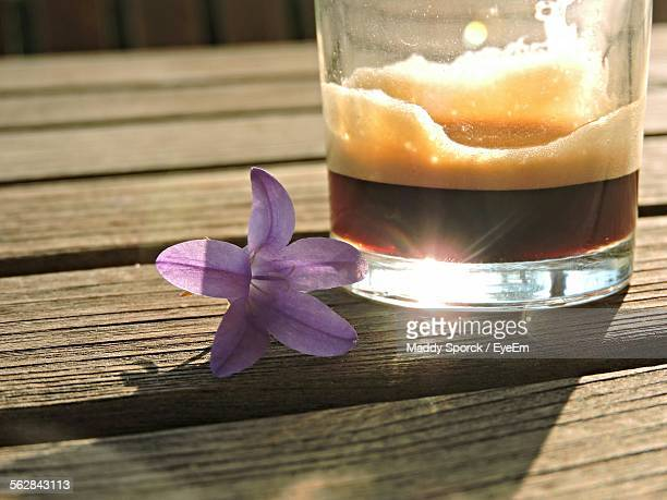 Close-Up Of Purple Flower With Espresso On Table