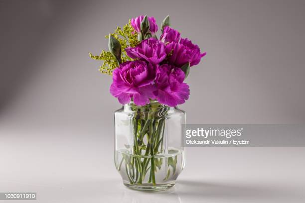 Close-Up Of Purple Flowers In Vase Against Gray Background