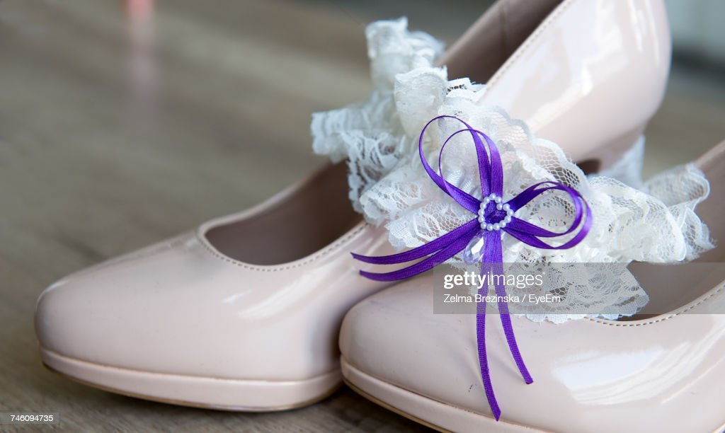 Close-Up Of Purple Tied Ribbon On White Lace Garter Over High Heels : Stock Photo