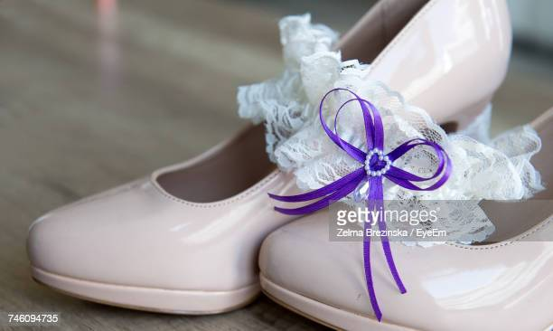 close-up of purple tied ribbon on white lace garter over high heels - bound in high heels stock photos and pictures