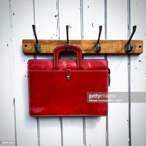 close-up of purse hanging on hook - red purse stock pictures, royalty-free photos & images