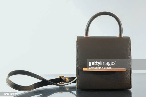 close-up of purse on table against white background - grey purse stock pictures, royalty-free photos & images
