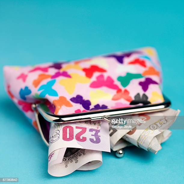 close-up of purse with money english pounds sticking out - twenty pound note stock pictures, royalty-free photos & images