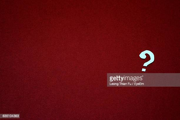 Close-Up Of Question Mark Over Red Background