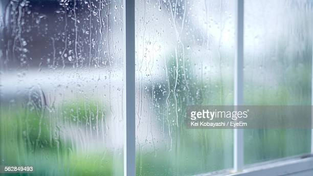 Close-Up Of Rain Drops On Glass Of Window