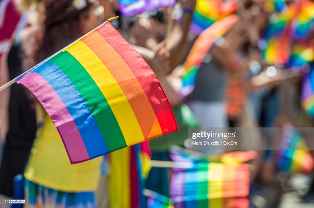 Close-Up Of Rainbow Flag With Crowd In Background During Parade : ストックフォト
