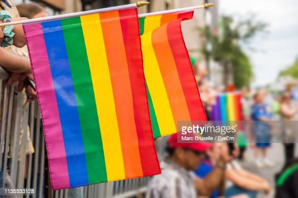 close-up of rainbow flags with crowd in background during parade - pride flag stock pictures, royalty-free photos & images