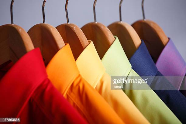 Close-up of rainbow shirt collars hanging in closet