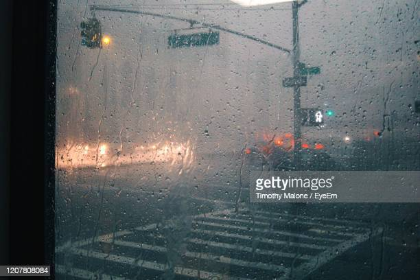 close-up of raindrops on glass window with urban street in background - walk don't walk signal stock pictures, royalty-free photos & images
