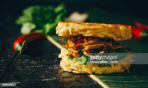 Close-Up Of Ramen Burger With Chicken On Banana Leaf