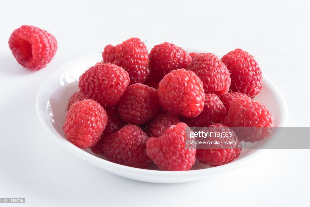 Close-Up Of Raspberries In Bowl Over White Background : Stock Photo