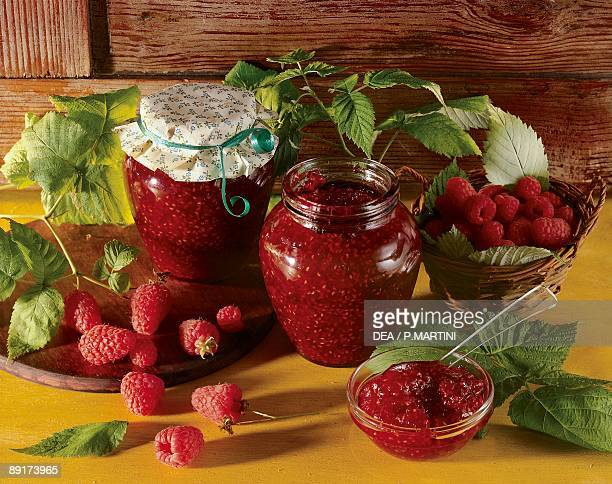 Closeup of raspberries with two jars of raspberry jam