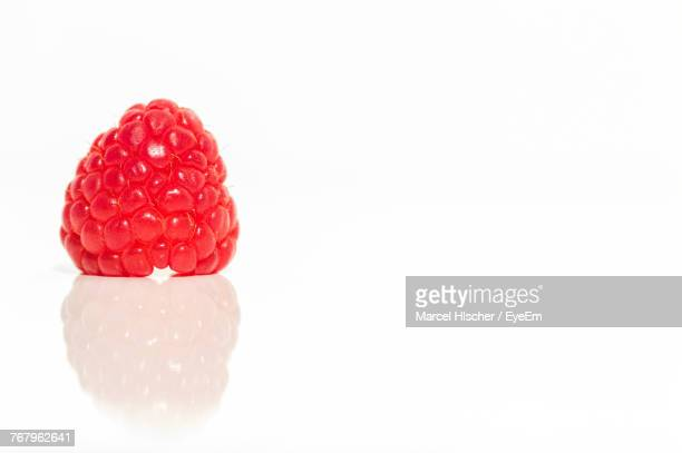 Close-Up Of Raspberry Against White Background