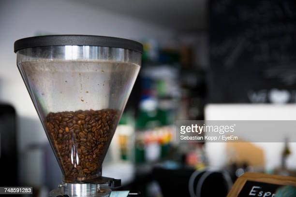 close-up of raw coffee beans in grinder - coffee grinder stock photos and pictures