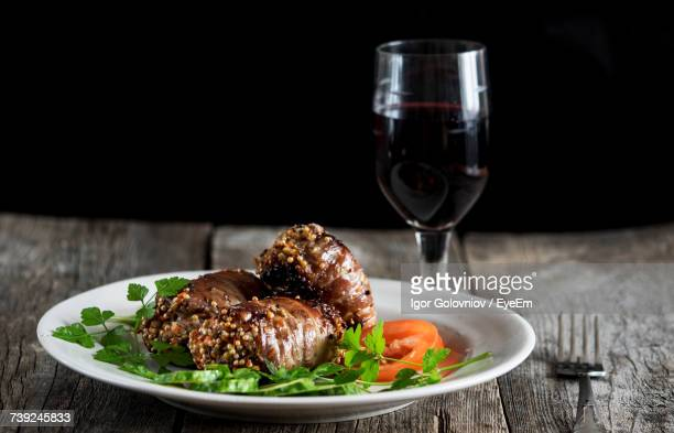 close-up of raw meatloaf in bacon on wooden table against black background - igor golovniov stock pictures, royalty-free photos & images