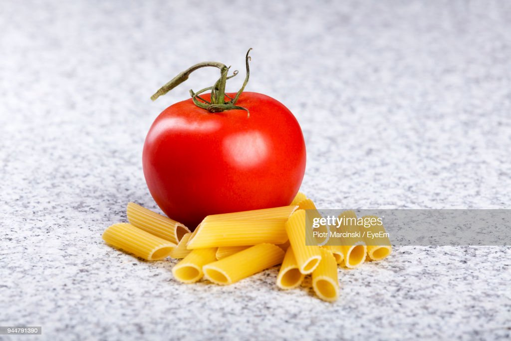 Close-Up Of Raw Pasta With Tomato On Table : Stock Photo