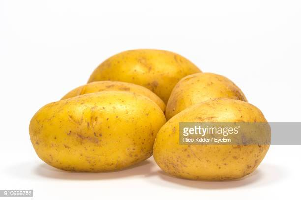 close-up of raw potatoes against white background - raw potato stock pictures, royalty-free photos & images