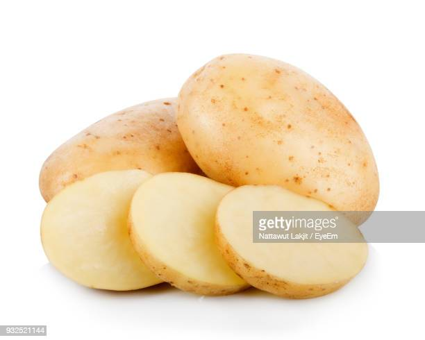 close-up of raw potatoes with slices against white background - raw potato stock pictures, royalty-free photos & images
