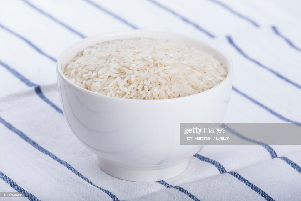 Close-Up Of Raw Rice In Bowl On Tablecloth : Stock Photo