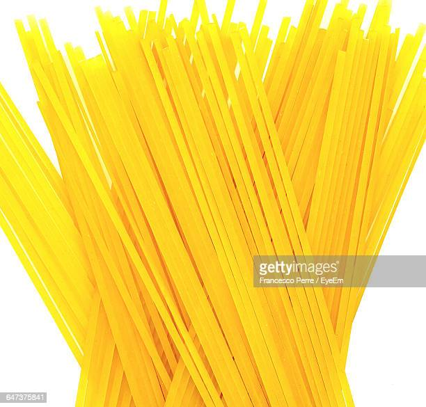 Close-Up Of Raw Spaghetti Against White Background