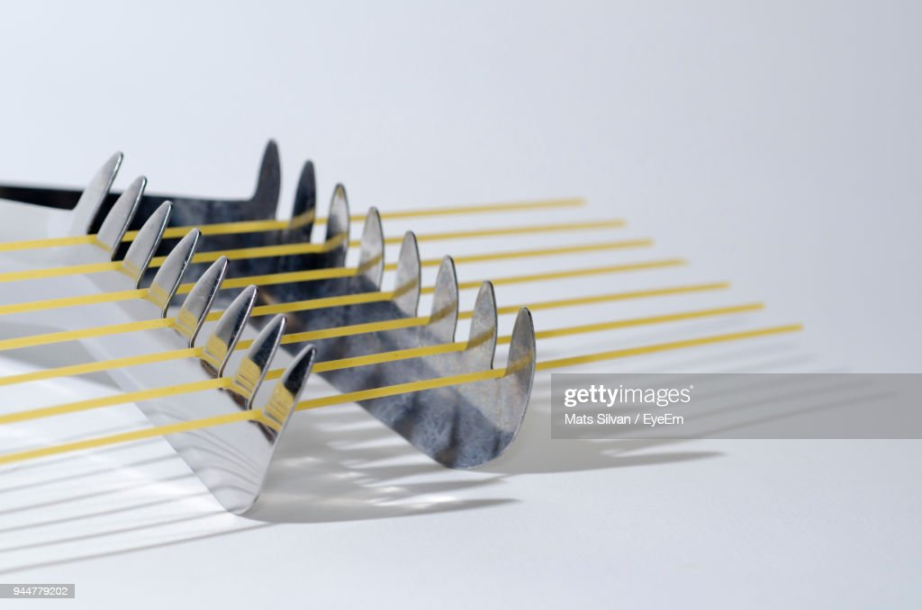 Close-Up Of Raw Spaghetti In Serving Tongs Against White Background : Stock Photo