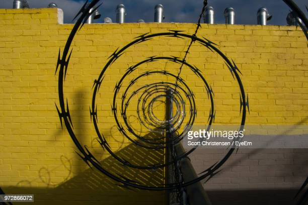 Close-Up Of Razor Wires Against Yellow Brick Wall