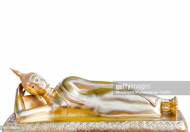 Close-Up Of Reclining Buddha Statue Over White Background