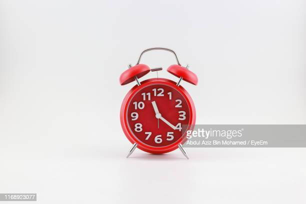 close-up of red alarm clock against gray background - alarm clock stock pictures, royalty-free photos & images
