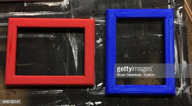 Close-Up Of Red And Blue Picture Frames On Table