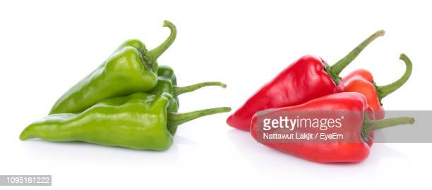 close-up of red and green chili pepper against white background - paprika stock pictures, royalty-free photos & images