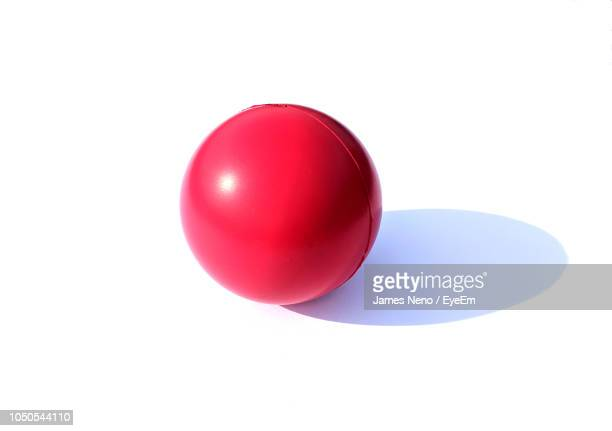 close-up of red ball against white background - sports ball stock pictures, royalty-free photos & images