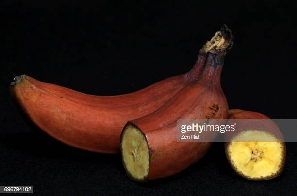 Close-up of Red Bananas cross section and whole against black background -Cavendish bananas