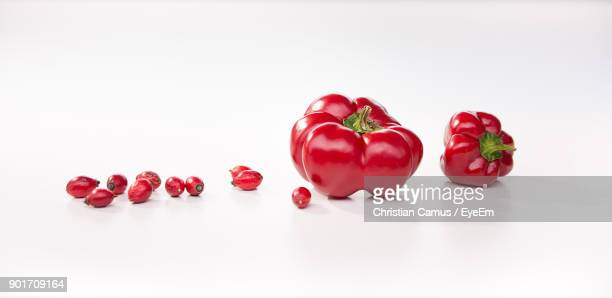 Close-Up Of Red Bell Peppers By Rose Hips Over White Background