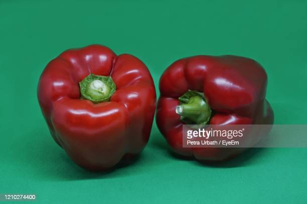close-up of red bell peppers on green background - petra bell stock-fotos und bilder