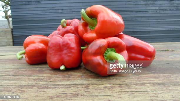 close-up of red bell peppers on table - keith savage stock-fotos und bilder