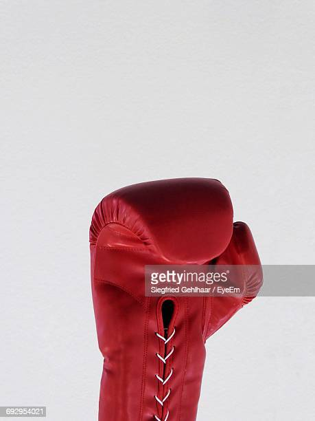 close-up of red boxing glove against white background - boxing gloves stock photos and pictures