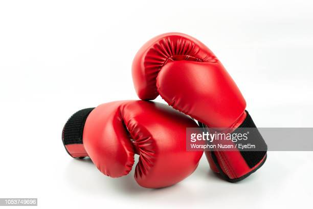 close-up of red boxing gloves against white background - boxing gloves stock photos and pictures