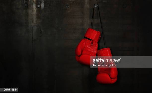 close-up of red boxing gloves hanging on wall - boxing gloves stock pictures, royalty-free photos & images