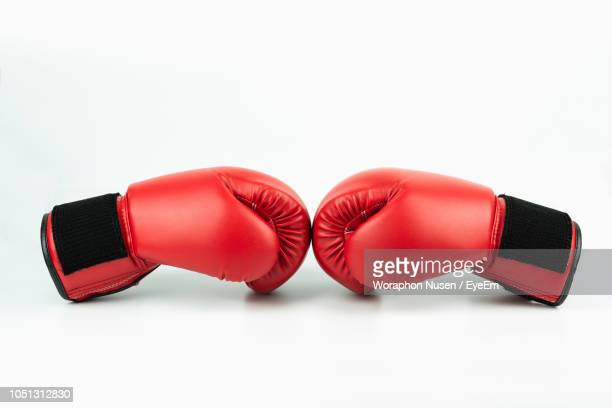 close-up of red boxing gloves over white background - boxing gloves stock photos and pictures