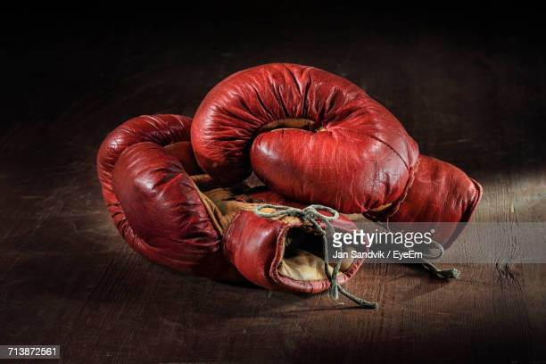 close-up of red boxing gloves over wooden background - boxing gloves stock photos and pictures