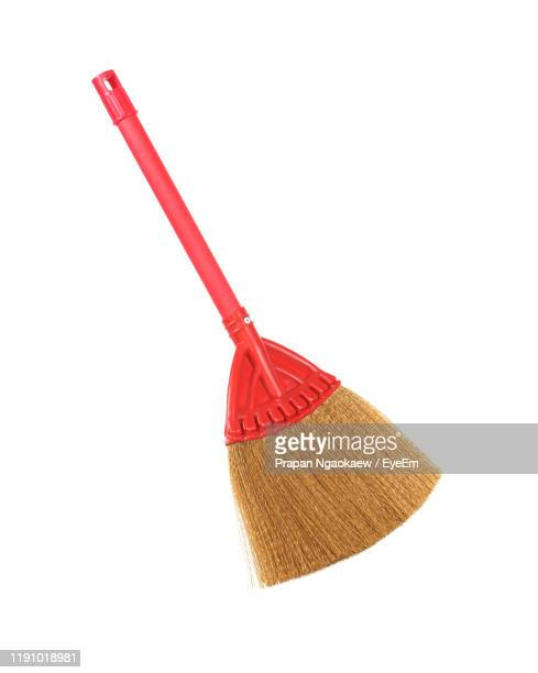 close-up of red broomstick against white background - broom stock pictures, royalty-free photos & images