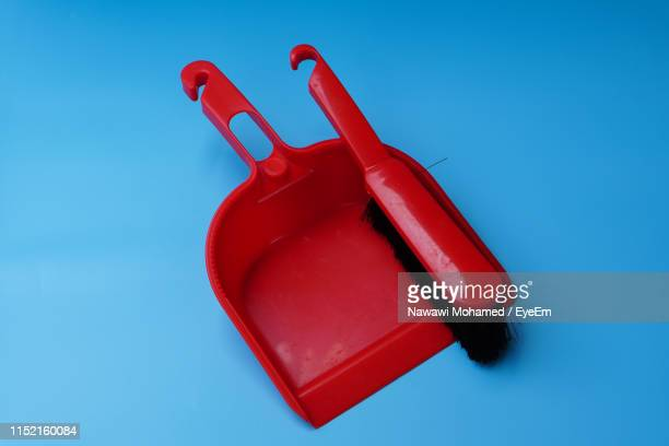 close-up of red brush and dustpan on blue background - objet rouge photos et images de collection