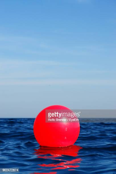close-up of red buoy floating on sea against blue sky - buoy stock photos and pictures