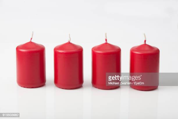 close-up of red candles arranged over white background - bougie photos et images de collection