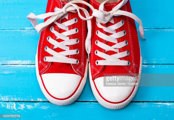 close-up of red canvas shoes on blue table - pair stock pictures, royalty-free photos & images