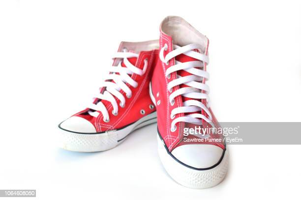 close-up of red canvas shoes over white background - canvas shoe stock pictures, royalty-free photos & images